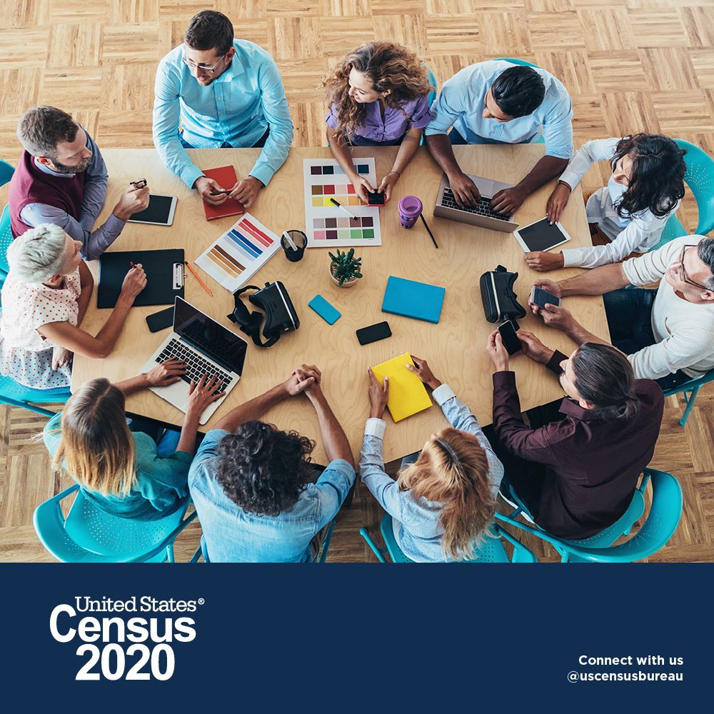 People around a table with office supplies as they discuss Census 2020
